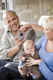 Parents with baby at home, dad holding camera Royalty Free Stock Images