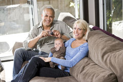 Parents and baby on lap at home, dad with camera Royalty Free Stock Photo