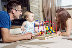 Parents baby sitting on floor play with toy Stock Images