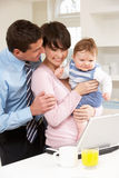 Parents With Baby Working From Home Using Laptop Stock Photos
