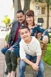 Parents Behind Their Cute Son on a Park Bench. Mixed Race Young Family Portrait At The Park royalty free stock photos