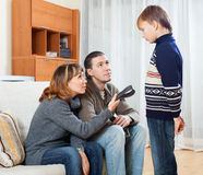 Parents with belt scolding teenager boy Stock Photos