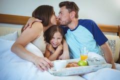 Parents besarse mientras que se sienta en cama con la hija y desayuna Imagen de archivo libre de regalías
