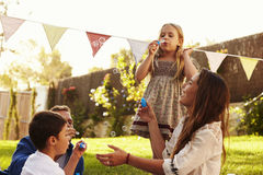 Parents Blowing Bubbles With Children In Garden Stock Images