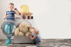 Parents bought a new washing machine. The children try to turn it on and wash the soft toys. Happy boys are playing at home.  Stock Photos