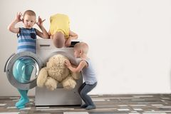 Parents bought a new washing machine. The children try to turn it on and wash the soft toys. Happy boys are playing at home.  Royalty Free Stock Photo