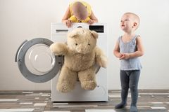 Parents bought a new washing machine. The children try to turn it on and wash the soft toys. Happy boys are playing at home.  Stock Photography
