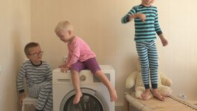 Parents bought new washing machine of new model latest generation. Children try to turn it on and wash soft toys. Three Happy boys. Are playing at home. Social stock video footage