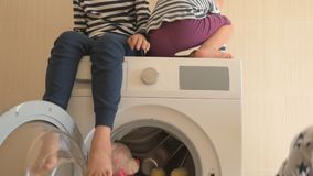 Parents bought new washing machine of new model latest generation. Children try to turn it on and wash soft toys. Three Happy boys are playing at home. Social stock video footage