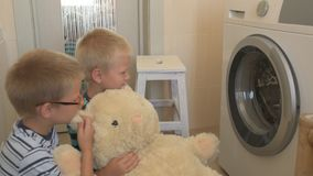 Parents bought new washing machine of new model latest generation. Children try to turn it on and wash soft toys. Three Happy boys are playing at home. Social stock video