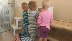Parents bought new washing machine of new model latest generation. Children try to turn it on and wash soft toys. Three Happy boys are playing at home. Social stock footage