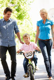 Parents with boy on bike. Learning to ride Royalty Free Stock Photos