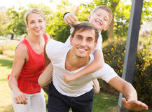 Parents with boy having fun. Glad young parents with boy in school age having fun and showing thumbs up outdoors Royalty Free Stock Image