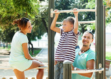 Parents with  boy training on pull-up bar Stock Image