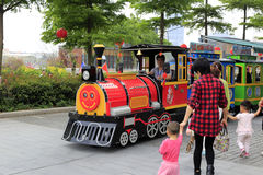 Parents bring the child to sit on a large toy train Stock Photos