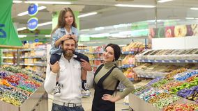 Parents buy sweets at the store,the daughter sits on the shoulders of her father. Young fashionable parents buy sweets at the store, the daughter sits on the stock video