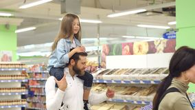 Parents buy sweets at the store, the daughter sits on shoulders of her father. Young fashionable parents buy sweets at the store, the daughter sits on the stock video