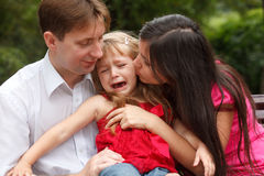 Parents calm crying girl on walk in summer garden Royalty Free Stock Photography
