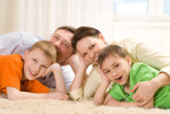 Parents are on the carpet with sons Stock Photography