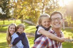 Parents carry their kids piggyback in a park selective focus Stock Photos
