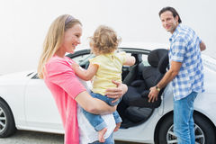 Parents carrying baby and her car seat Stock Photo
