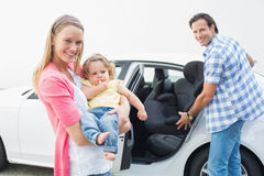 Parents carrying baby and her car seat Royalty Free Stock Image