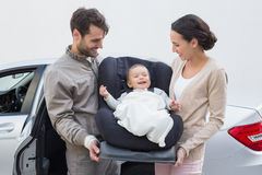 Parents carrying baby in his car seat Royalty Free Stock Images