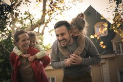 Parents carrying daughters on piggyback. Family enjoying in nature together Royalty Free Stock Photos