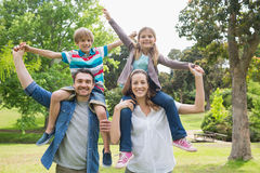 Parents carrying kids on shoulders at park Stock Photography