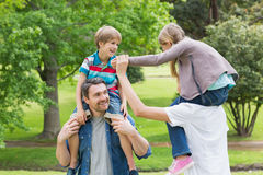 Parents carrying kids on shoulders at park Stock Image