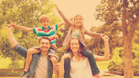 Parents carrying kids on shoulders at park. Portrait of happy parents carrying kids on shoulders at the park royalty free stock photo