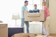 Parents carrying son on armchair in new house Royalty Free Stock Image