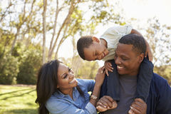 Parents Carrying Son On Shoulders As They Walk In Park Stock Image