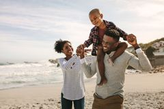 Parents carrying son on shoulders on beach vacation. African family of mother and father carrying son on his shoulders on vacation royalty free stock photos
