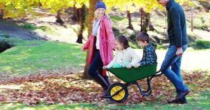 Parents carrying their son and daughter in a wheelbarrow stock footage