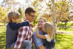 Parents carrying their two young children in a park Royalty Free Stock Photo