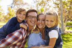 Parents carrying their two young kids in park look to camera Royalty Free Stock Image