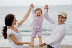 Parents and child. Portrait of happy couple holding their daughter by hands and feet and looking at camera Stock Photos