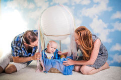 Parents with a child in a balloon. Parents with a child in a hot air balloon in the clouds Stock Image