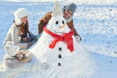 Parents and child build snowman. In winter as a family Stock Image