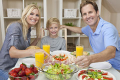 Parents Child Family Healthy Food At Dining Table. An attractive happy, smiling family of mother, father and son eating salad and healthy food at a dining table stock images