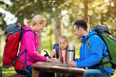 Parents and child girl look map in the forest Royalty Free Stock Photo