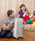 Parents and child near warm radiator. Parents and child relaxing near warm radiator in home royalty free stock images