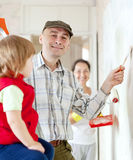 Parents with child  paints wall at home Royalty Free Stock Photo