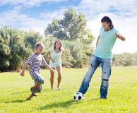 Parents with child playing with soccer ball. Happy parents with child playing with soccer ball in summer Stock Image