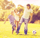 Parents with child playing with soccer ball Royalty Free Stock Photos