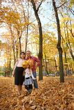Parents and child are posing in autumn city park. Bright yellow trees royalty free stock image