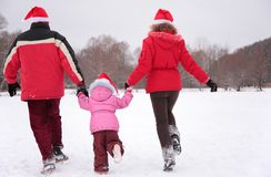 Parents with child run in winter from back Royalty Free Stock Photos