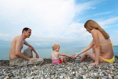 Parents with child on sea coast build pyramid Royalty Free Stock Photo