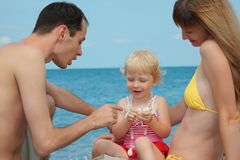 Parents with child on sea shore Stock Image